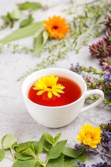 Taza de té de hierbas con caléndula, lavanda, orégano, hisopo, menta y bálsamo de limón, vista lateral.