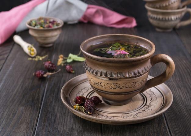 Taza de té de hierbas caliente con rosas de cadera, manzanilla, hierbas en la mesa de madera