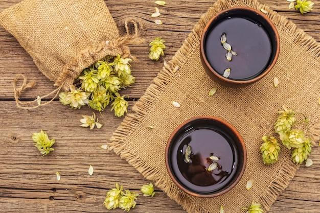 Taza de té de hierbas calmante con lúpulo fresco. conos de lúpulo en saco sobre tableros vintage
