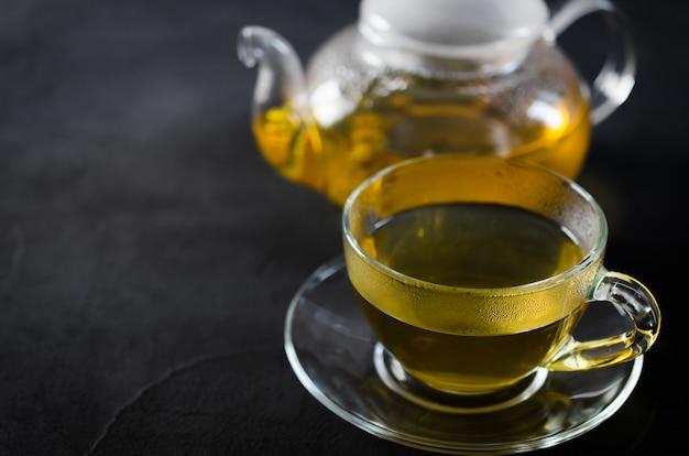 Taza de té de hierbas delicioso y tetera de vidrio.