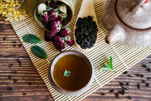 Taza de té de hierbas con flor de rosa seca y hojas secas sobre mantel individual