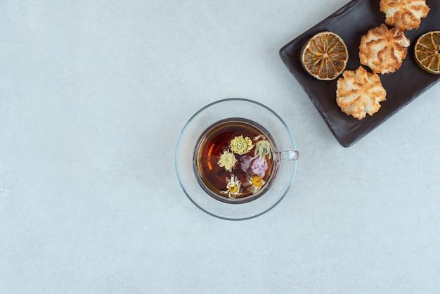 Una taza de té de hierbas con galletas y naranjas secas en placa negra.