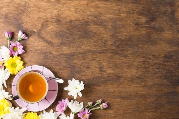 Taza de té de hierbas y hermosas flores en la esquina del fondo de madera