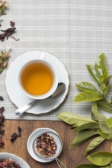 Taza de té de hierbas; hierbas secas y hojas en mantel sobre la mesa.