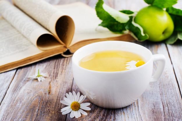 Taza de té de hierbas y libro antiguo