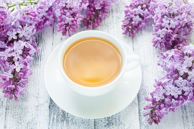 Taza de té de hierbas y lila sobre fondo de madera