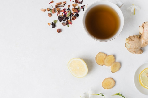 Taza de té de hierbas con limón; jengibre; ingredientes de flores y pétalos secos sobre fondo blanco