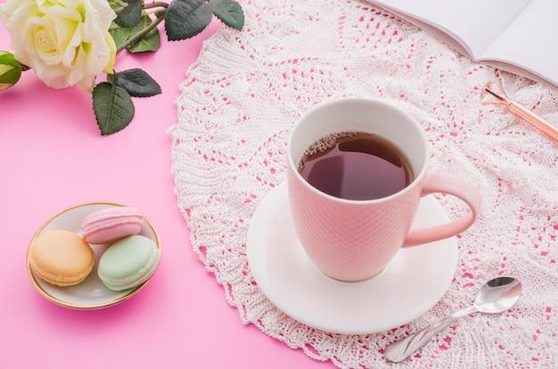 Taza de té de hierbas con macarrones; cuchara; rosa; pluma y libro sobre fondo rosa