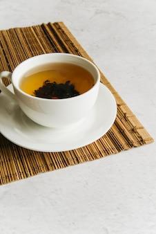Taza de té de hierbas en mantel individual sobre el fondo de hormigón