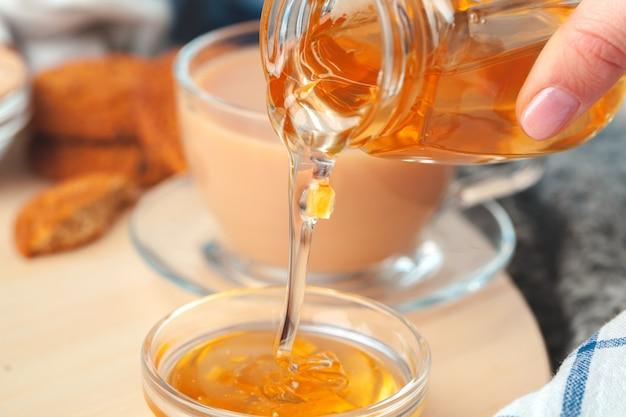 Taza con té de hierbas y miel y té de hierbas seco.