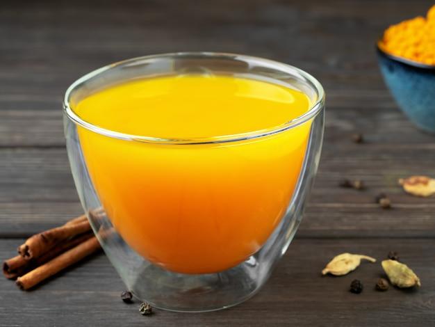 Taza con té de hierbas naturales y saludables a base de cúrcuma, miel y especias