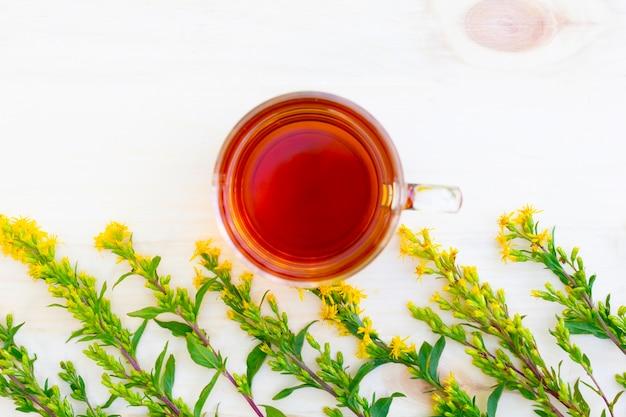 La taza de té de hierbas negro con ramas de hypericum o tutsan en mesa de madera