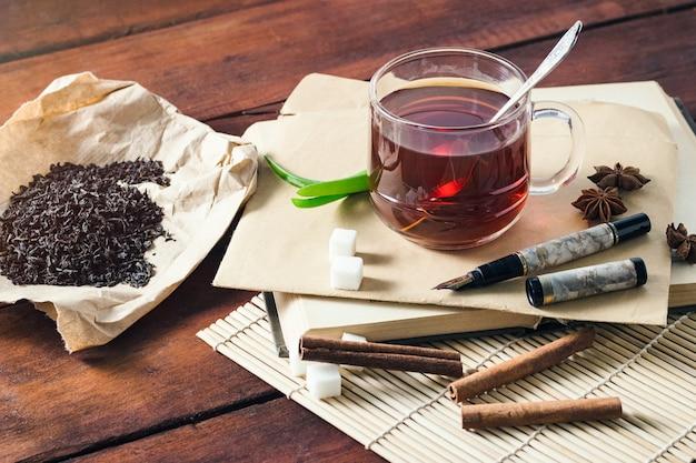 Taza con té, hojas de té secas sobre papel artesanal, sobre de rebanadas de azúcar y manija sobre una mesa de madera