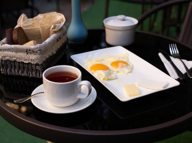 Una taza de té y huevos fritos sobre la mesa negra.