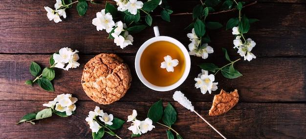 Taza de té con jazmín y galletas sobre un fondo de madera. banner largo
