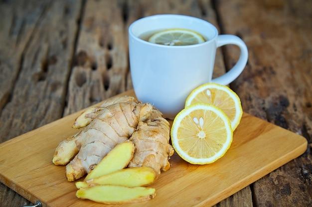 Taza de té de jengibre con limón en madera
