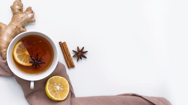 Taza de té con jengibre sobre tela marrón