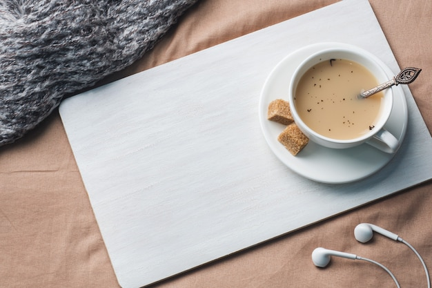 Taza de té con leche, azúcar de anís marrón y un bloc de notas.