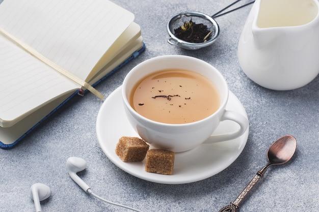 Taza de té con leche, azúcar de anís marrón y un cuaderno en una mesa gris.