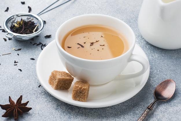 Taza de té con leche, azúcar de anís marrón sobre una mesa gris.