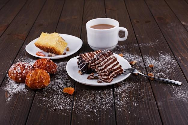 Taza de té con leche y dos platos con tarta de queso y chocolate