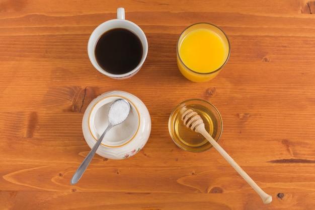 Taza de te leche en polvo; jugo de naranja y miel en escritorio de madera