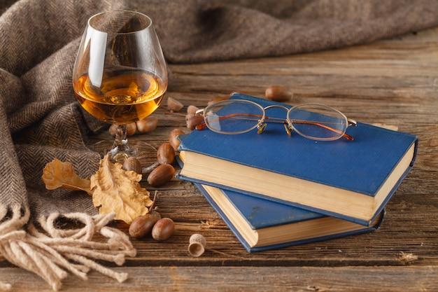 Taza de té con libro viejo, hojas de otoño en mesa de madera