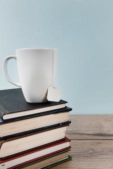 Taza de té en libros con espacio de copia