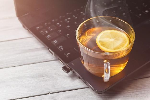Taza de té con limón en la computadora portátil y el concepto de mesa de madera blanca de la hora del té, relajarse con espacio de copia