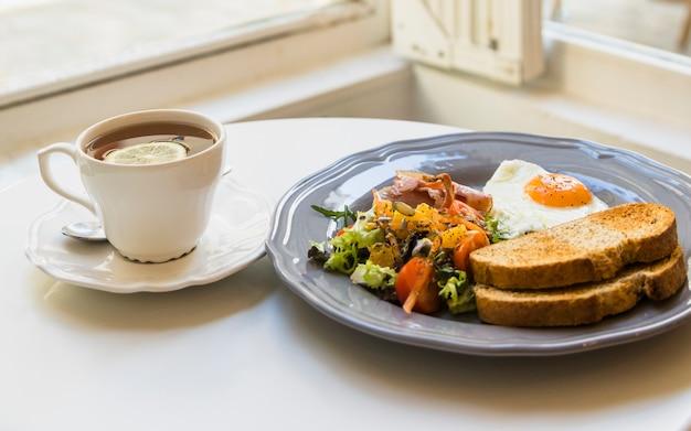 Taza de té de limón y desayuno en mesa redonda blanca