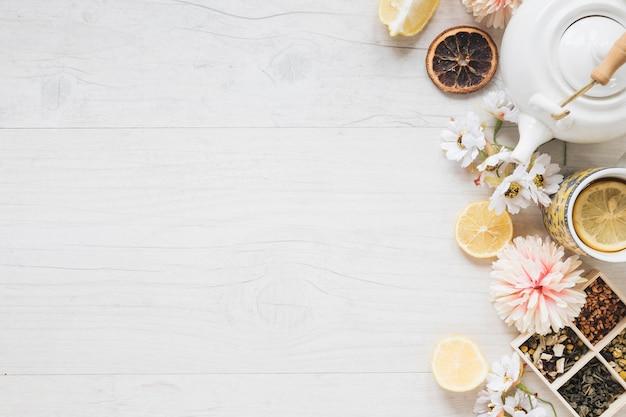 Una taza de té de limón; flores frescas; hierbas; hojas secas de te; tetera y rodaja de limón en mesa de madera blanca