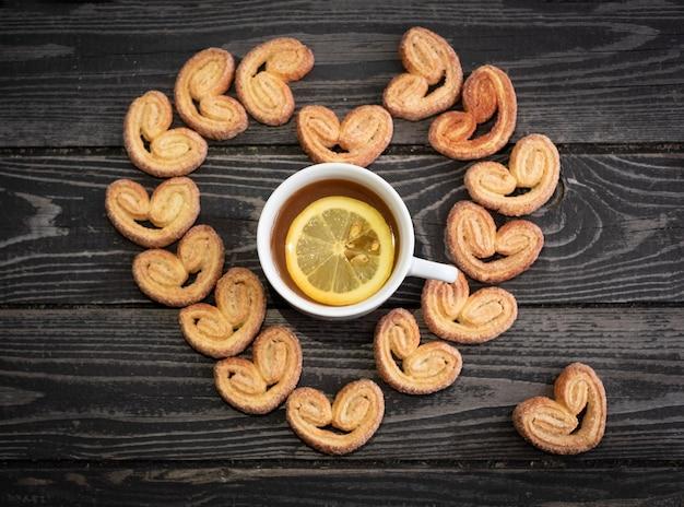 Taza de té con limón y galletas en forma de corazón