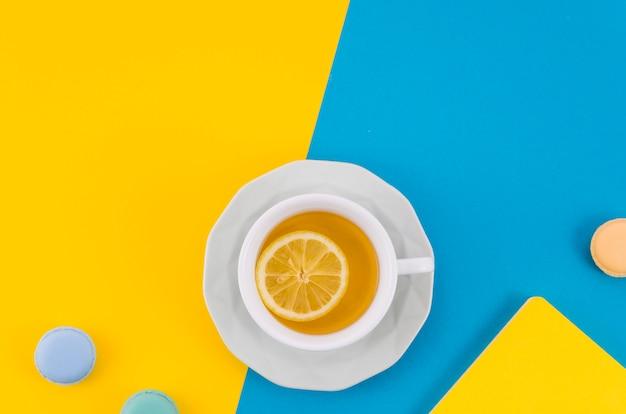 Taza de té de limón con macarrones sobre fondo doble amarillo y azul