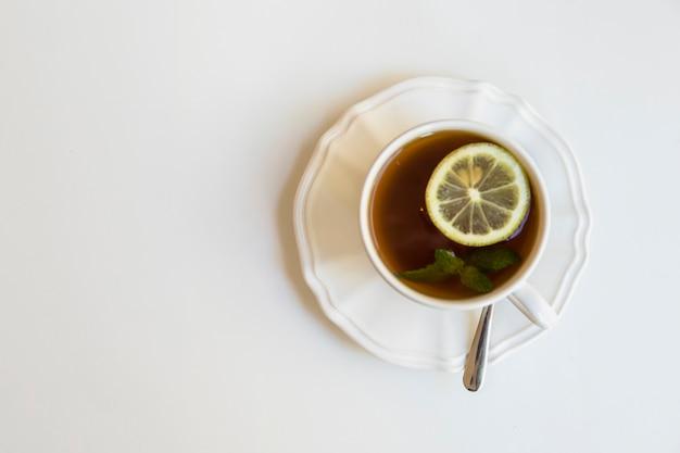 Taza de té de limón y menta; cuchara en plato de cerámica sobre fondo blanco