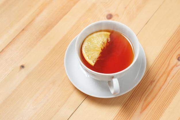 Taza de té con limón en la mesa de madera