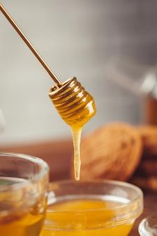 Taza de té con limón y miel en madera.