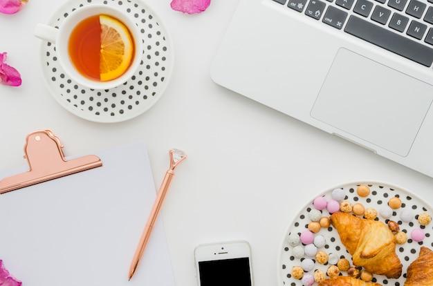 Taza de té de limón; ordenador portátil; cuerno; golosinas; teléfono móvil; pluma y portapapeles sobre fondo blanco