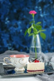 Una taza de té con el limón y los pasteles en un fondo azul. descanso
