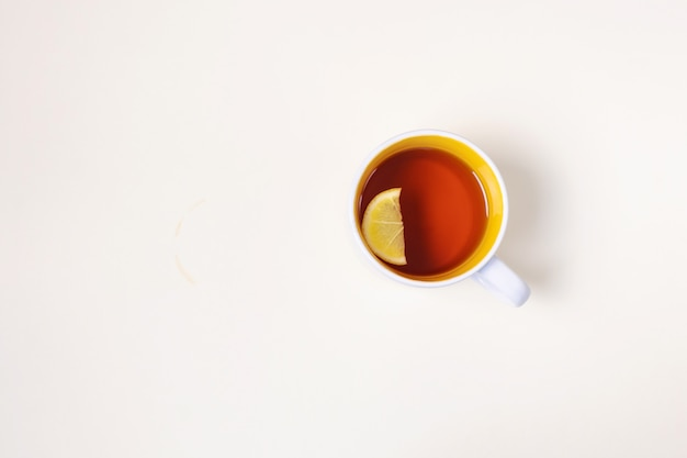 Taza con té con limón sobre un fondo beige.