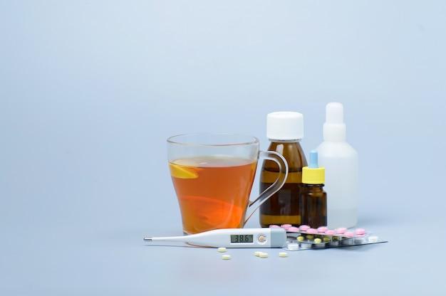 Taza de té con limón, termómetro y drogas.