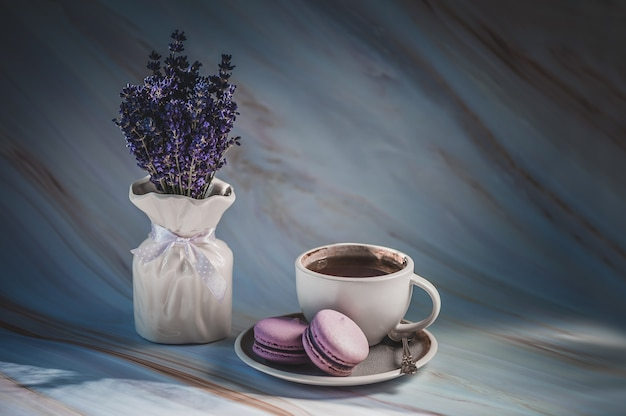 Taza de té con macarons de lavanda en textura. postre francés delicado.