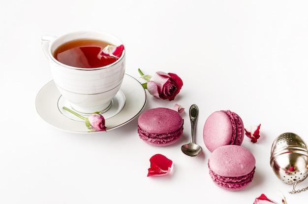 Taza de té con macarons y rosas sobre fondo blanco.