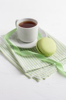 Taza de té y macarrones franceses verdes sobre una madera blanca