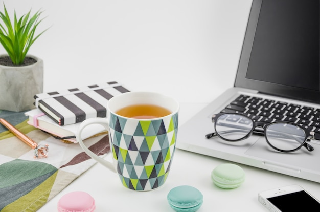 Taza de té con macarrones en la mesa de trabajo blanca con computadora portátil y teléfono móvil