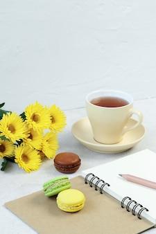 Taza de té, macarrones y notas sobre mesa de hormigón.