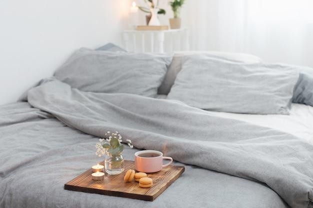Taza de té con macarrones y velas en bandeja de madera en la cama