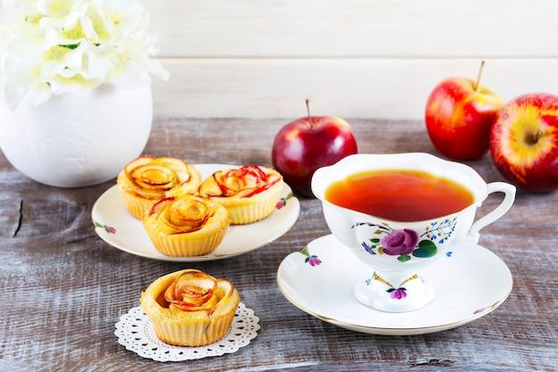 Taza de té y magdalenas con rodajas de manzana en forma de rosa