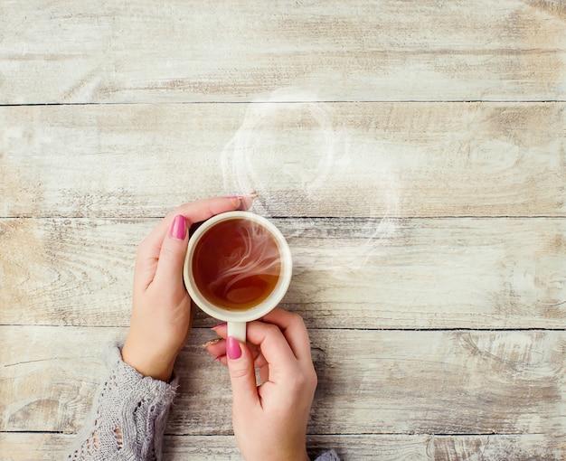 Una taza de té en manos de un hombre y una mujer. enfoque selectivo