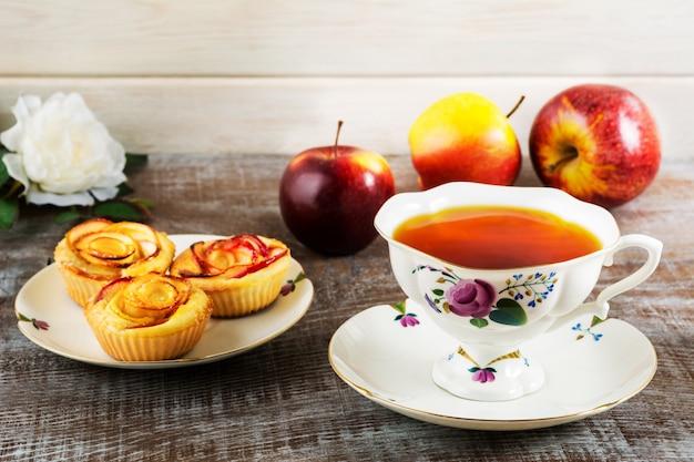 Taza de té y manzana magdalenas en forma de rosa