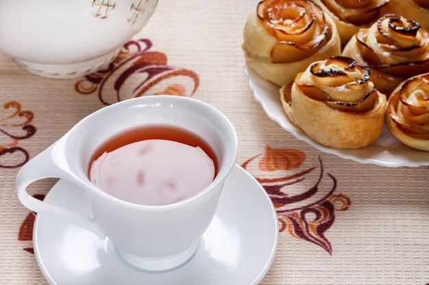 Una taza de té de manzana con un platillo con panecillos horneados en un pla